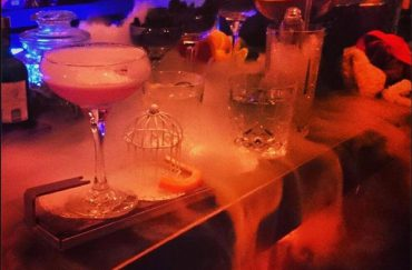 Dry ice smoking between cocktails on a bar.