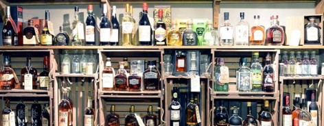 Photograph of shelves stacked with bottles of spirit.