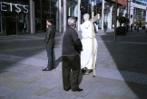 A man in white drags a cross through Spinningfields