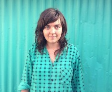 Singer Courtney Barnet in a turquoise shirt against a turquoise background