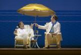Robert Lindsay and Rufus Hound in Dirty Rotten Scoundrels - on beach chairs beneath a yellow umbrella
