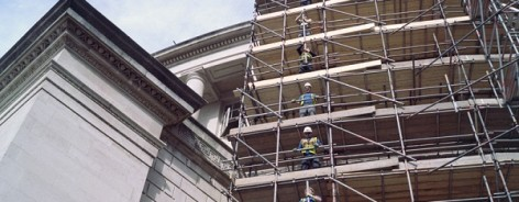 Scaffolders drop a pole between them on levels of scaffolding around Central Library