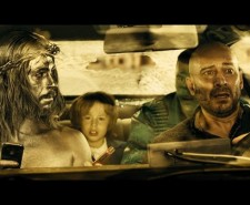 Screen shot from Witching and Bitching with two men in the front of a car, one painted silver.