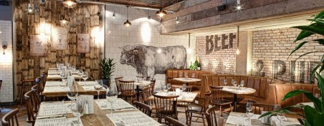 Photograph of Beef and Pudding's interior, with a bull printed on white tiles on the back wall