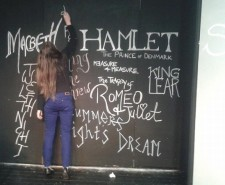 Photograph of a woman in blue trousers writing up productions on a blackboard