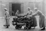 Black and white photo of women pushing a wooden trolley