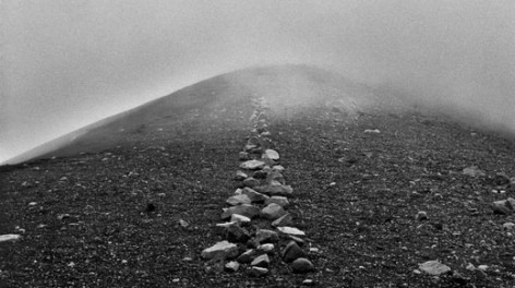 Black and white image of a Richard Long art piece; stones leading into mist.