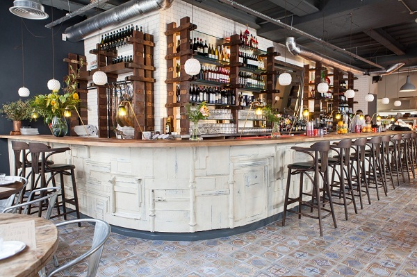 Photo of Bacaro's white fronted bar, with wooden bar stools