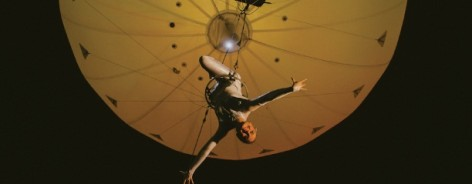 Photo of a trapeze artist hanging beneath a yellowy balloon