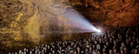 Photo of a crowd of people watching a film in a cave