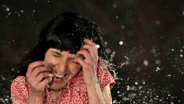 Photo of a girl in a pink top having water splashed in her face.