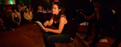 A woman reads from the page at the spring scratch night