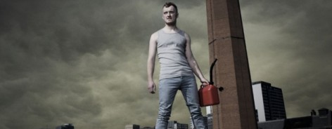Photo of a man holding a petrol can against a clouded sky