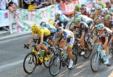 Photo of cyclists on the Tour de France, a man in front with a yellow helmet and jersey
