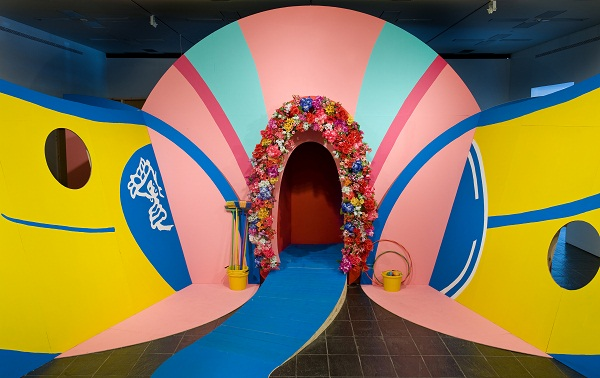 Photo of a Heather Phillipson installation, a walkway through a brightly coloured and suggestively shaped archway