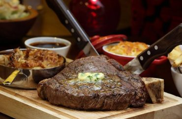 Photo of a steak with chive butter on a wooden board