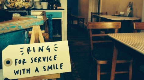 "Photo of a handwritten label in a cafe that says ""Ring for service with a smile"""