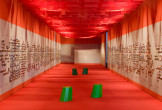 Photo of a long corridor with white walls, plastered with photos, and an orange ceiling and floor.