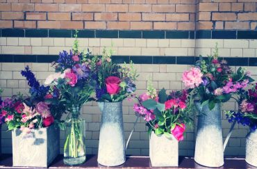 Photo of bouquets in jugs along a black and white painted brick wall