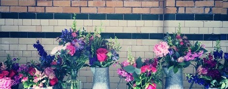 Photo of bouquets in jugs against a painted brick wall.