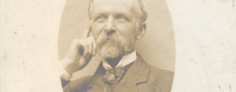 Sepia photo of Henry Watson with beard and moustache, hand on chin