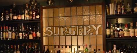Photo of a stained glass window showing the word 'Surgery'