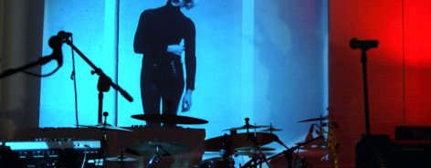 Photo of Kraak's event space with a coloured screen and drum kit