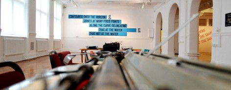 Photo along a row of typewriters, with a text art work on the back wall