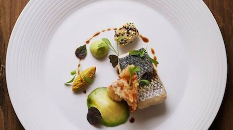 Photo of a fish dish, with avocado and a circular sauce.
