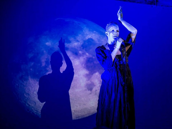 Photo of a silver painted woman performing in front of the image of a moon