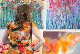 Photo of a woman in a colourful dress looking at a painting.