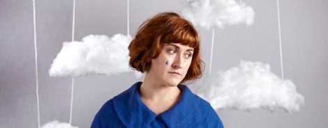 Photo of musician Liz Green in a blue jacket with handmade clouds hung around her