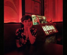 Red lit photo of singer in front of jukebox