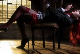 Photo of a red haired man reclining in stockings across a stool