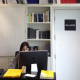 Image of a woman at her computer, with bookshelves behind her.
