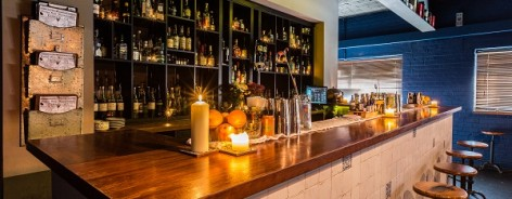 Photo of a white tiled bar lit with candles