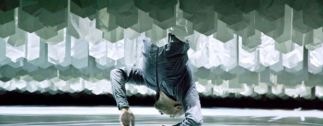 Photo of Akram Khan hanging upside down amid a maze of paper