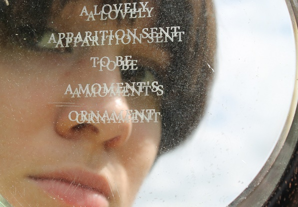 Photo of a mirror inscribed with words, with a woman's reflection in it
