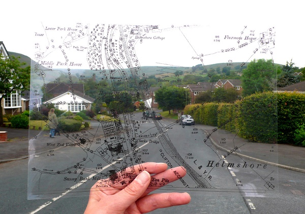 A hand holds a transparent map up to a countryside road
