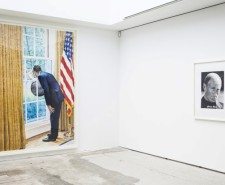 Photo with realistic painting of a man looking out of a window next to the American flag