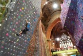 Photograph of a man scaling a climbing wall inside a church