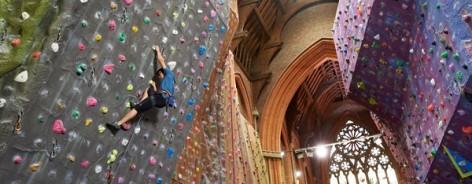 Photograph of a man scaling a climbing wall inside a church