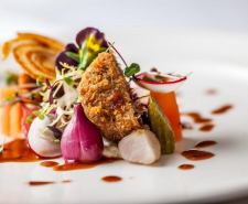 Photo of a plate of pork cheek with beetroom and a pansy flower