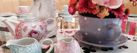 Photo of a giant teacup with artificial flowers, tableware and a giant chess piece