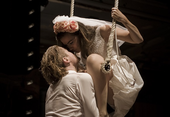Romeo kisses Juliet who is sitting on a swing