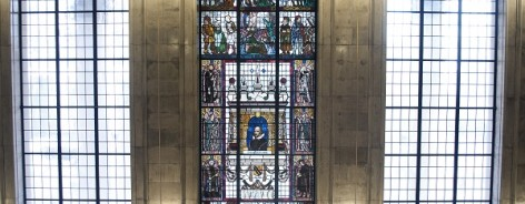 Photo of a stained glass window featuring Shakespeare and his characters