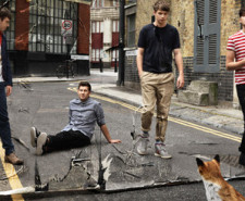 Photograph of the band Everything Everything in a street with a fox