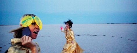 Photo of two wmoen wearing gold on a beach