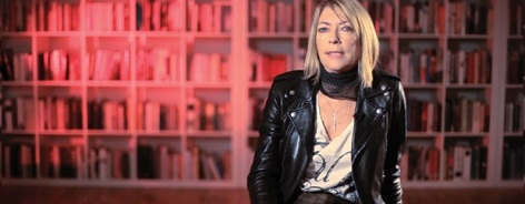 Photo of Kim Gordon with red bookshelves behind her