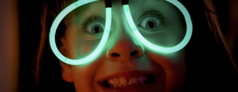 Photo of a kid wearing glow stick glasses